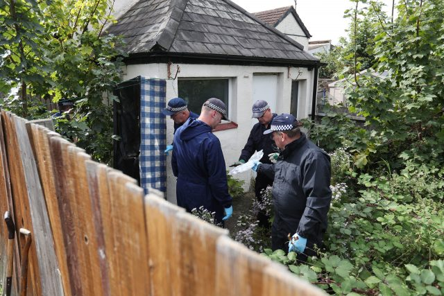 Police search the back of a property in Thornton Heath, south London ( Jonathan Brady/PA)