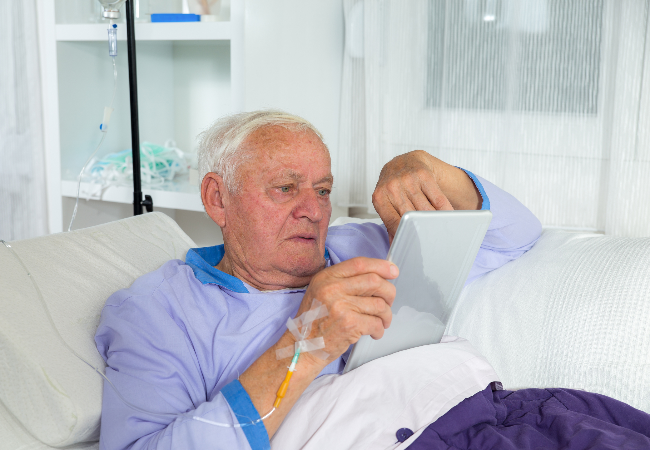 An elderly man with an infusion uses a tablet