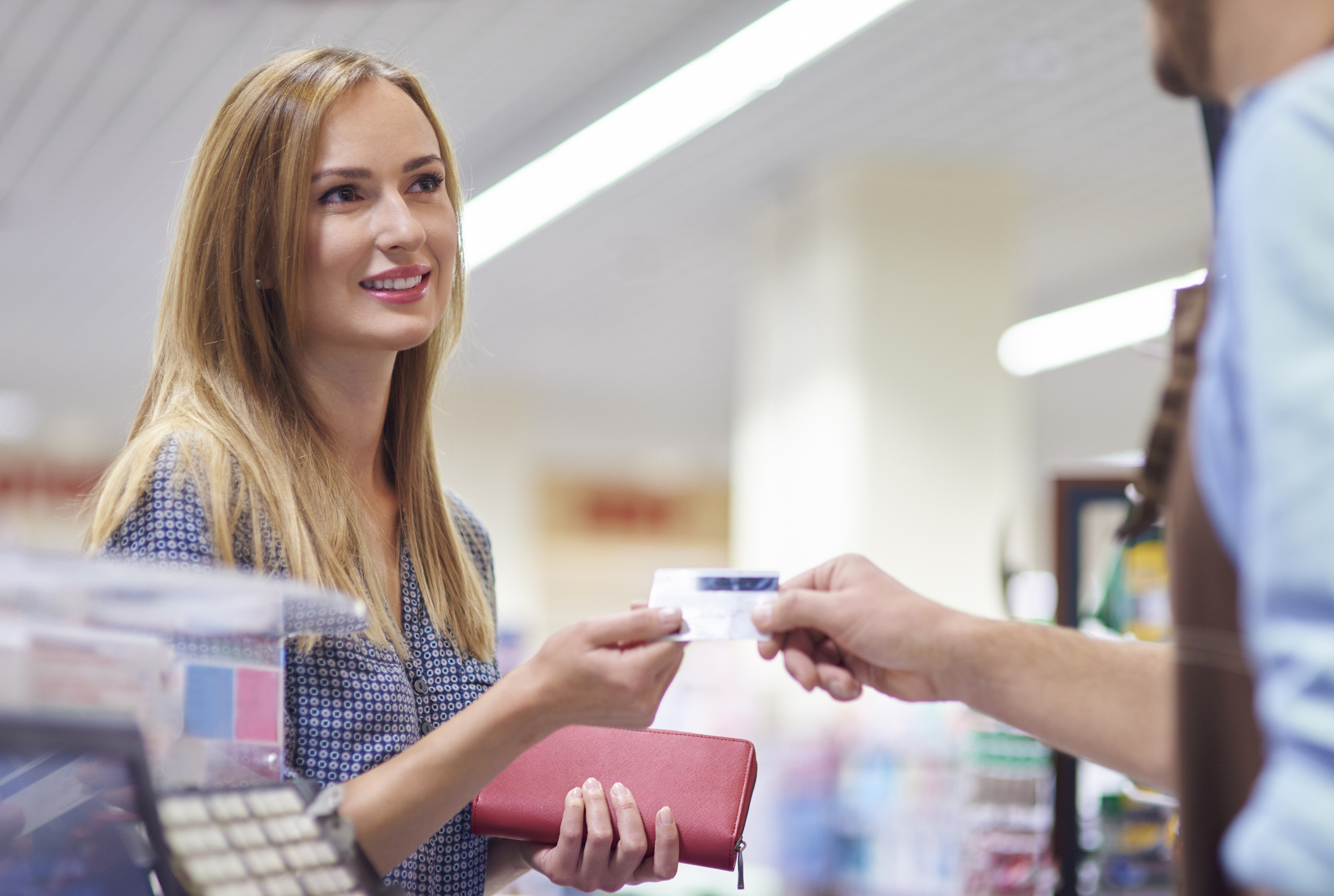 woman in a shop using a credit card to pay
