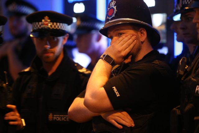 Police officers among mourners viewing tributes in St Ann's Square, Manchester