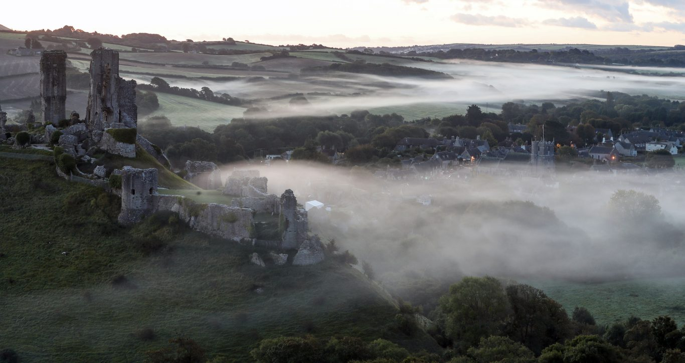 A low lying mist surrounds the village of Corfe Castle in Dorset on the day of the Autumn Equinox (Andrew Matthews/PA)