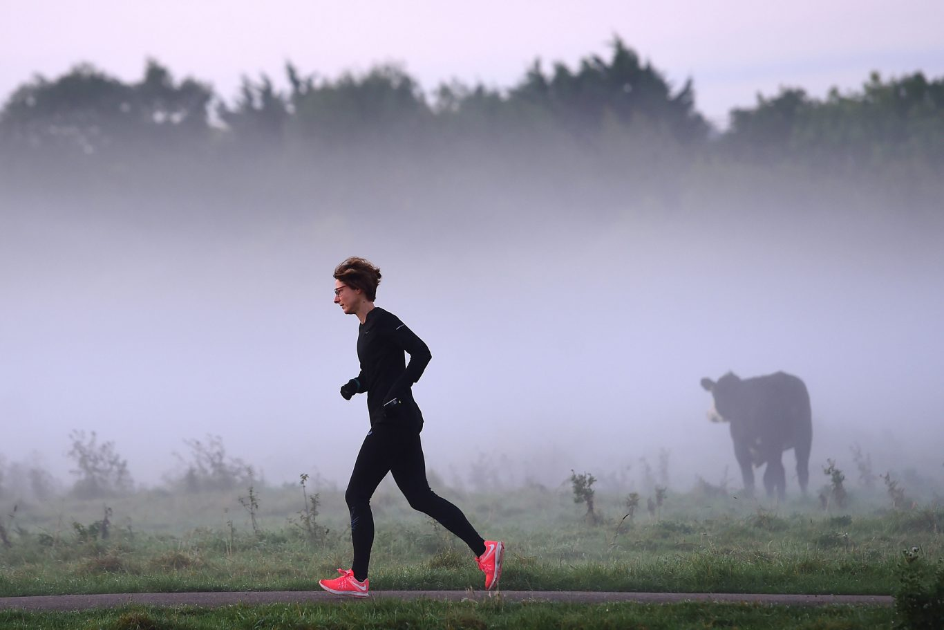 A woman runs past early morning mist along the River Cam in Cambridge on the day of the Autumn Equinox (Joe Giddens/PA)