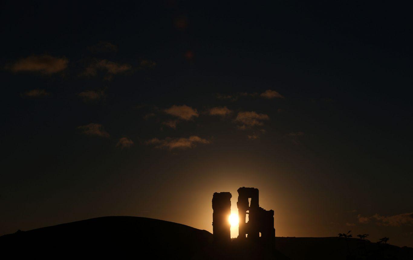 The sun rises behind Corfe Castle  in Dorset (Andrew Matthews/PA)
