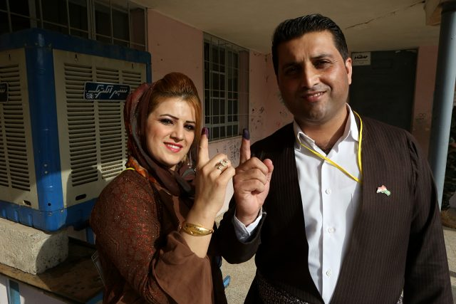 An Iraqi Kurdish man and woman show their inked fingers after casting a vote