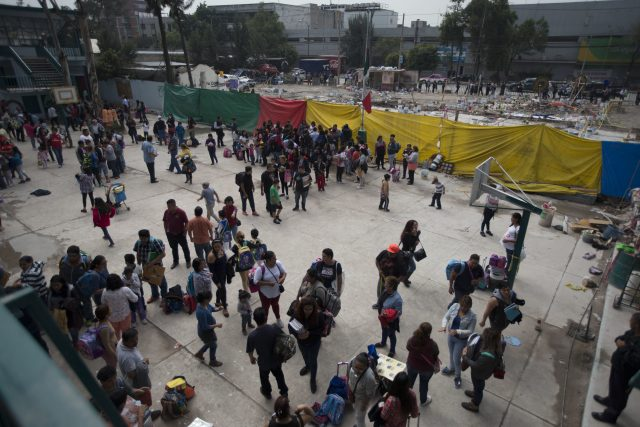 People gather near the site of a factory that collapsed in the earthquake in Mexico City