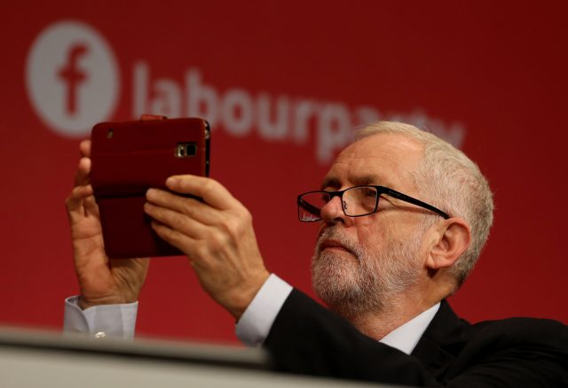 Jeremy Corbyn takes a photograph as he listens to speeches