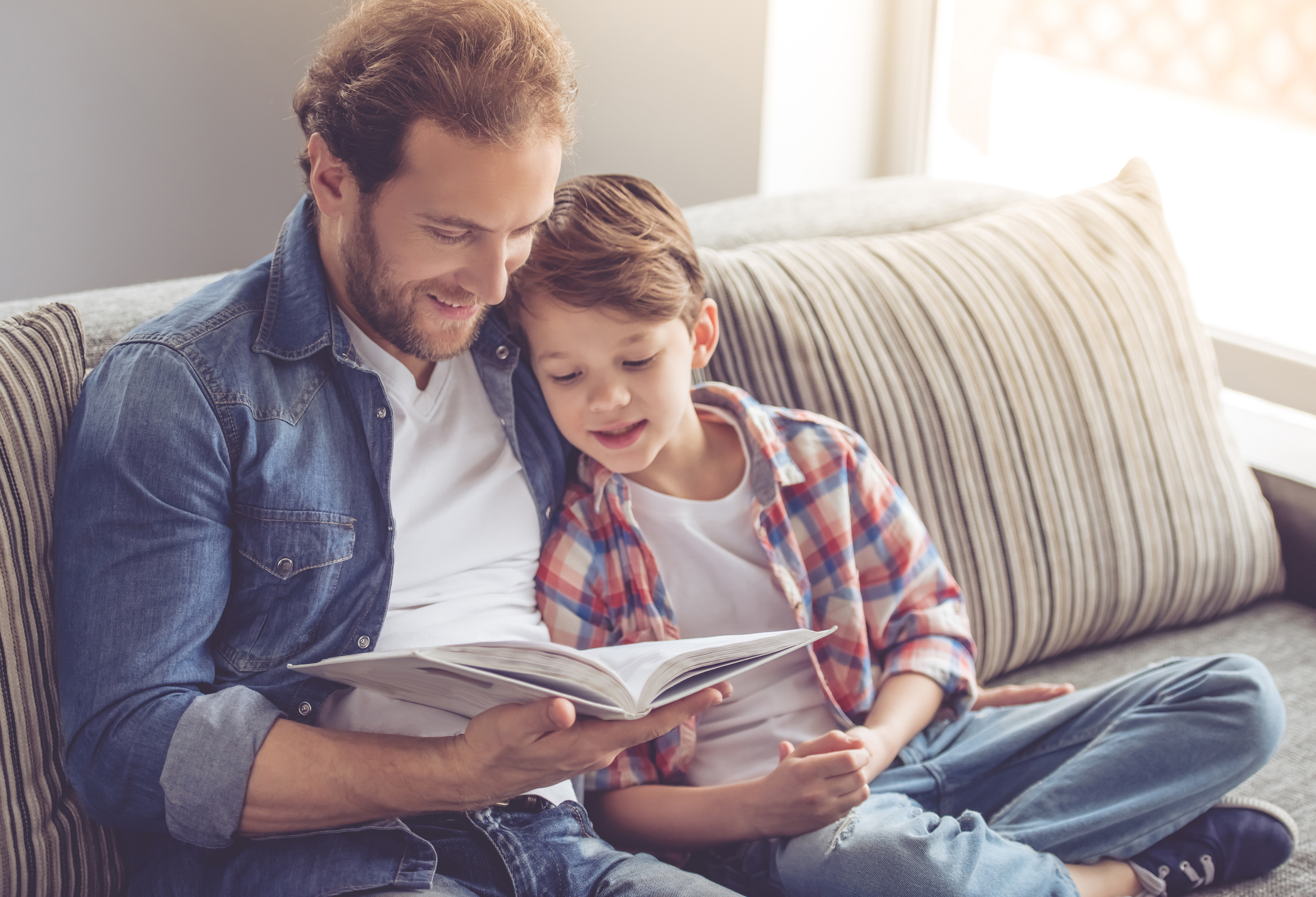 Father and son are reading a book and smiling while spending time together at home (Thinkstock/PA)
