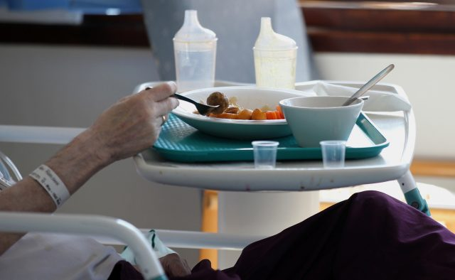 A patient eats a hospital meal