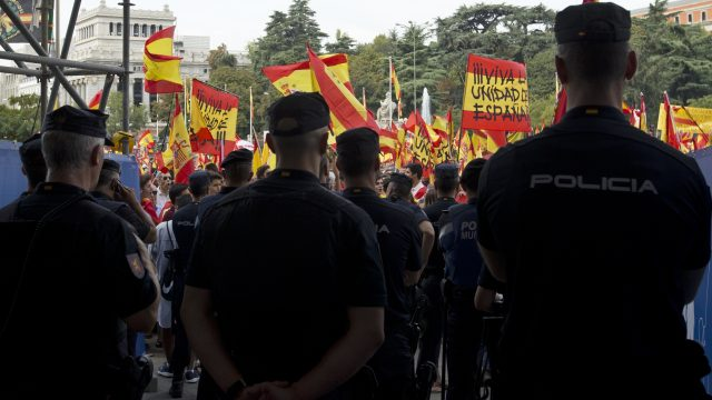 Police block the entrance of the city hall as protesters wave Spanish national flags in the central Cibeles square in Madrid