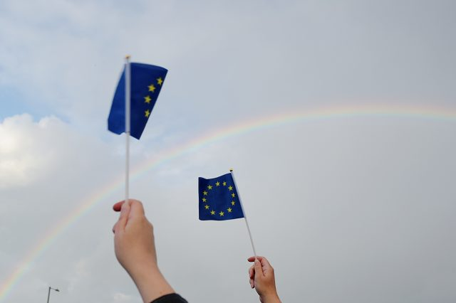 Supporters hold up European Union flags as a rainbow forms in the sky