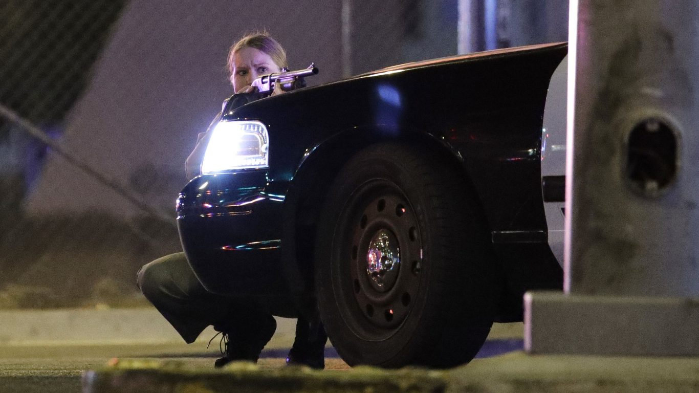 A police officer takes cover behind a police vehicle during a shooting near the Mandalay Bay resort and casino on the Las Vegas Strip (John Locher/AP)