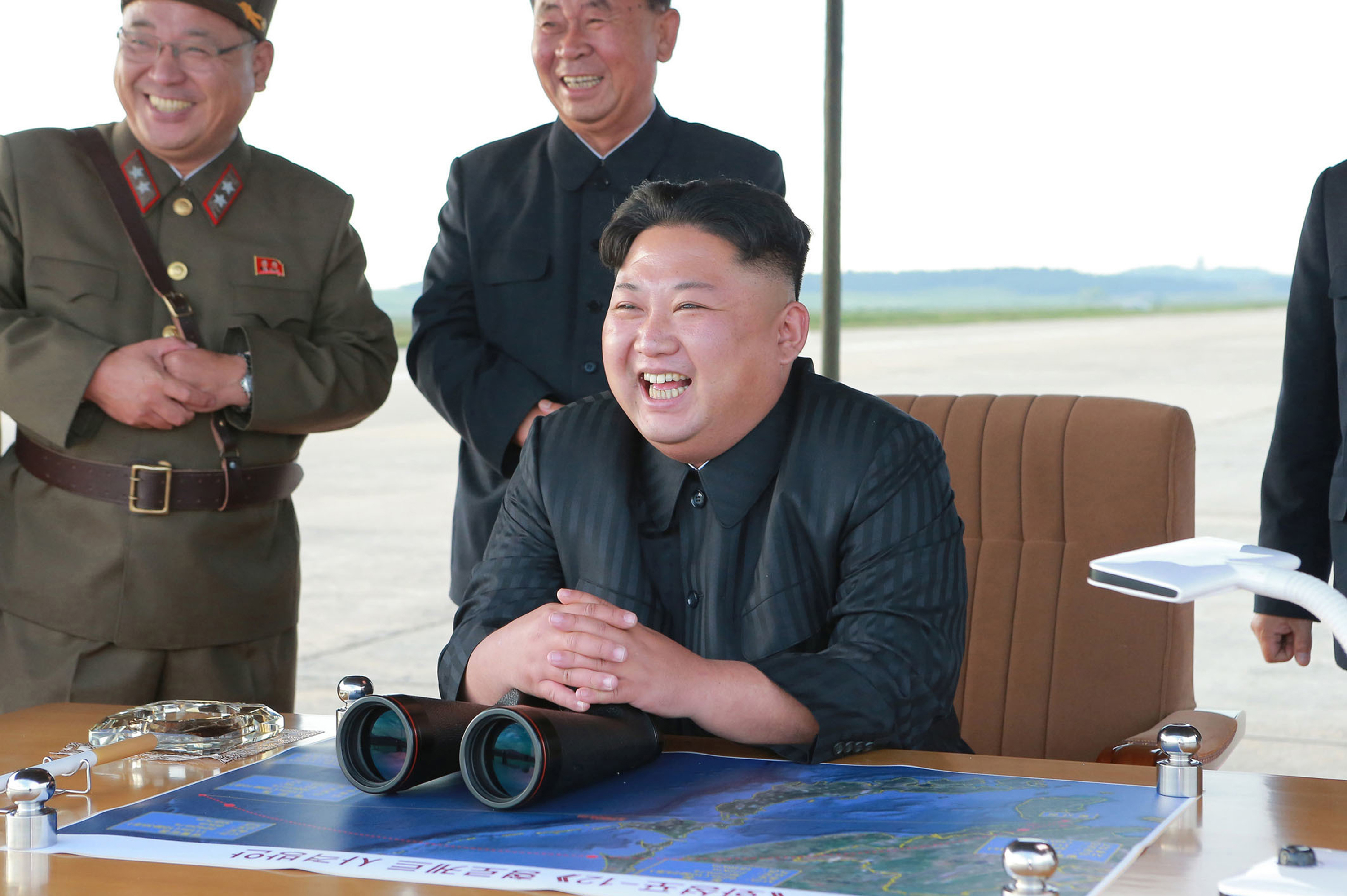 Kim Jong Un laughs at what the North Korean government said was a missile test