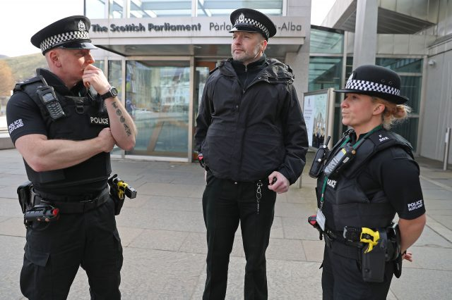 Police officers with Tasers outside Scottish Parliament in Edinburgh. (PA)