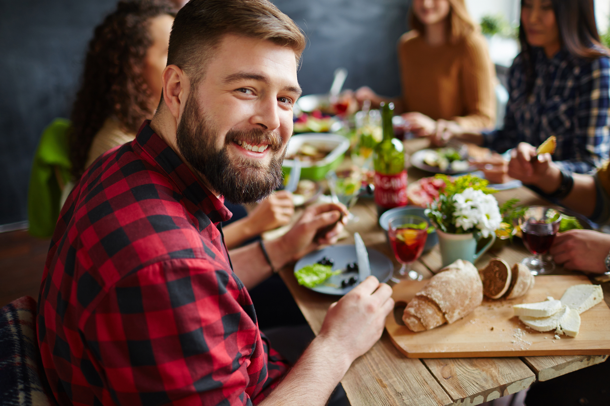 Young man sitting at dinner table with his friends and smiling at camera (Thinkstock/PA)