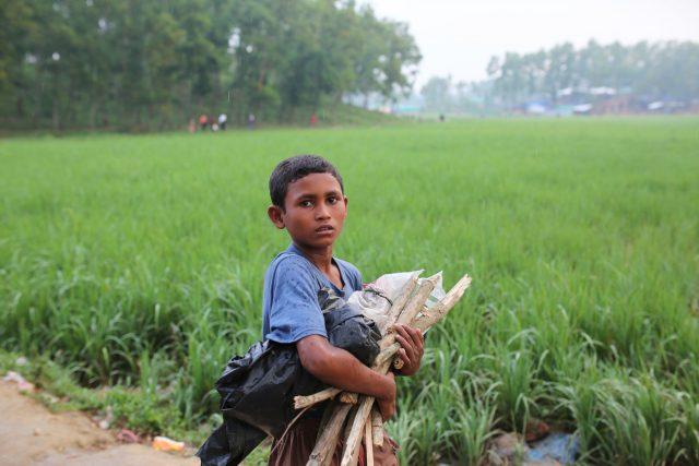 A Rohingya child walks with firewood near Kutupalong refugee camp in Cox's Bazar, Bangladesh