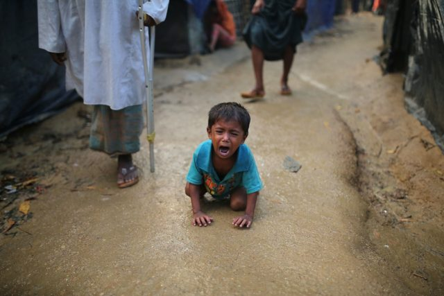 A Rohingya child cries kneeling on the ground at a makeshift camp near Kutupalong refugee camp in Cox's Bazar, Bangladesh