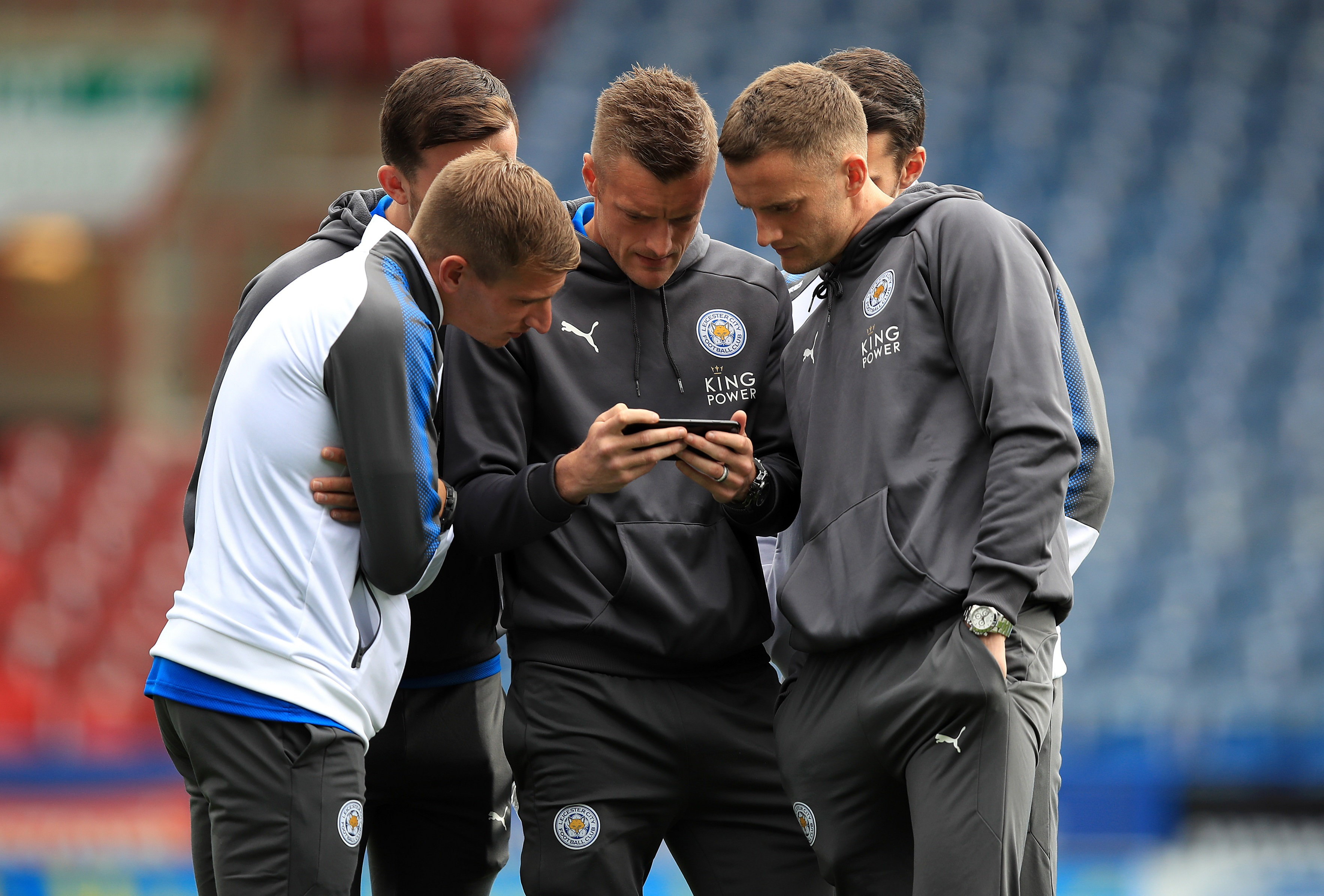 Jamie Vardy and his Leicester team mates look at a phone