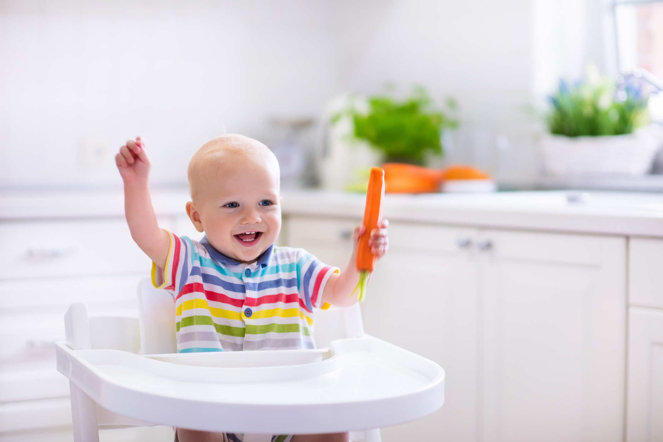 Happy baby sitting in high chair eating carrot in a white kitchen (Thinkstock/PA)