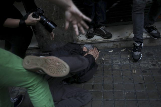 A protester falls on the ground after being hit in the face by a rubber bullet