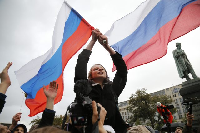 Demonstrators wave Russian flags during a rally in Moscow