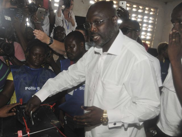 Former soccer star George Weah, presidential candidate for the Coalition for Democratic Change, casts his vote