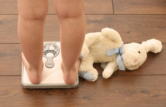 A girl using a set of weighing scales