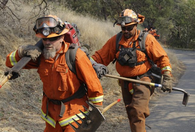 Firefighters walk through charred ground