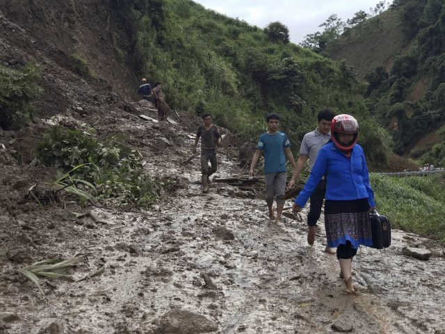 Residents walk along a muddy road which was damaged by a landslide in Vietnam