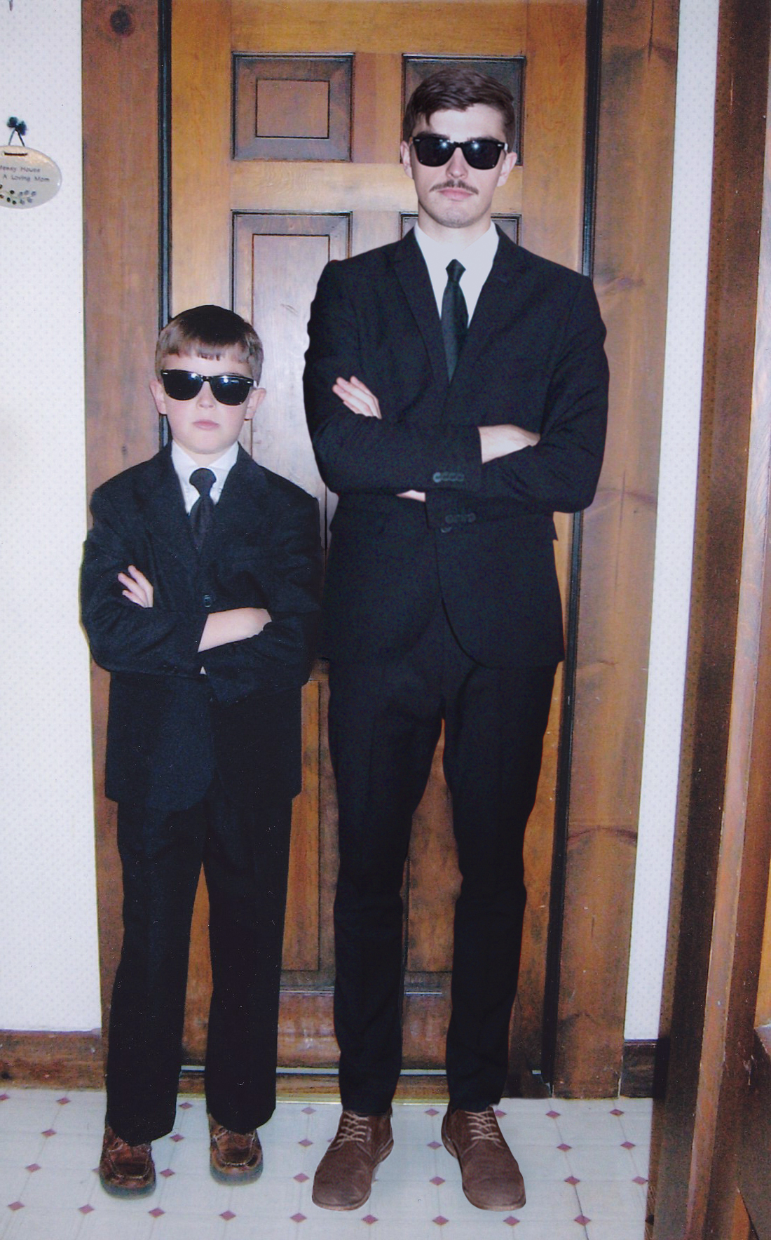 Conor and his younger self in suits with sunglasses