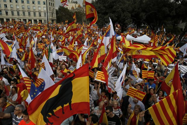 People wave flags of Catalonia and Spain as they celebrate Spain's National Day in Barcelona