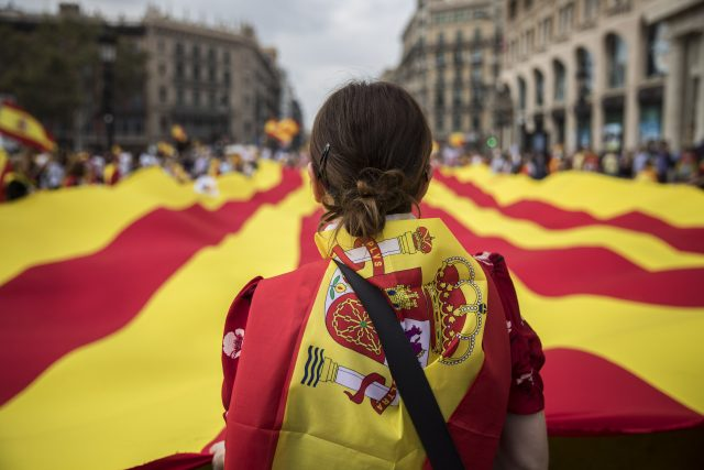 A woman wearing a Spanish flag looks at a giant flag of Catalonia
