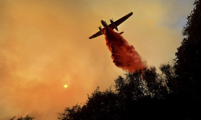 A pilot works to protect properties from the wildfires