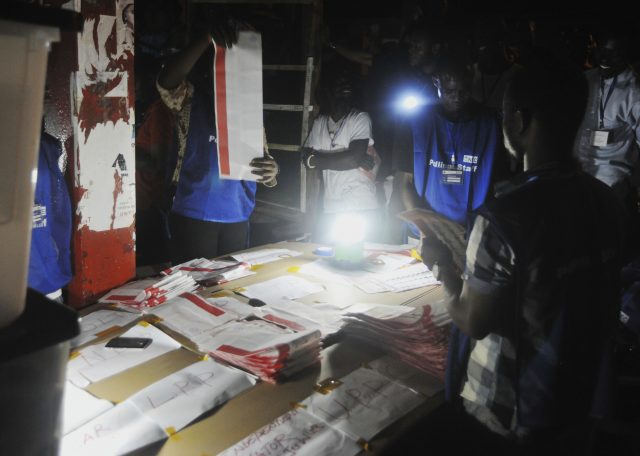 Electoral officials use a lantern as they count ballot papers at the end of voting at a polling station in Monrovia