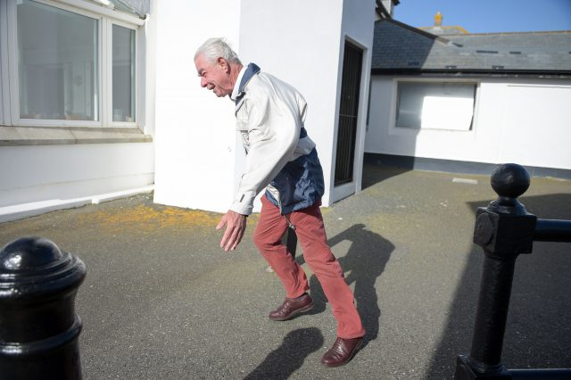 A man struggles to walk in strong winds at Lands End, Cornwall