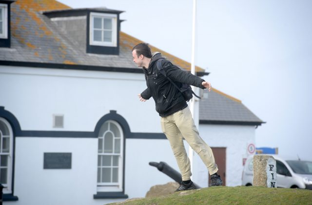 A man struggles to stand up in strong winds in Cornwall