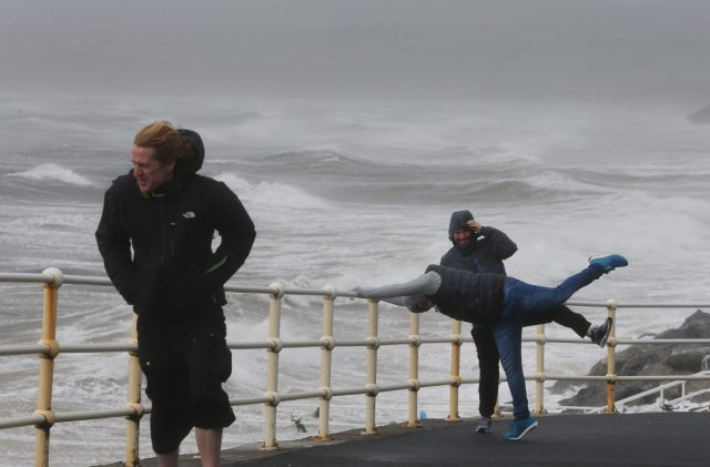 People battle the waves and high wind at Lahinch in County Clare on the West Coast of Ireland