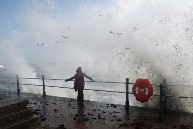 A woman walks past waves crashing on the sea wall at Penzanze, Cornwall