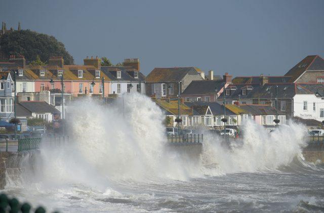 Waves break on the sea wall at Penzanze, Cornwall