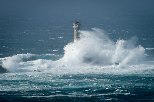 Waves break on Longships lighthouse off the coast of Lands End, Cornwall