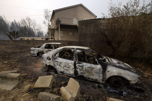 Burnt cars sit next to a house near Penacova, northern Portugal
