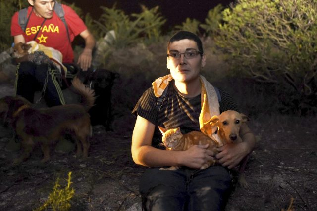 Residents hold their pets as a wild fire moves forward their houses in As Neves, Pontevedra, in the northwestern Spanish region of Galicia