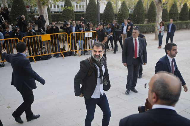 Jordi Cuixart, president of the Catalan Omnium Cultural organization, center, smiles on arrival at the national court in Madrid