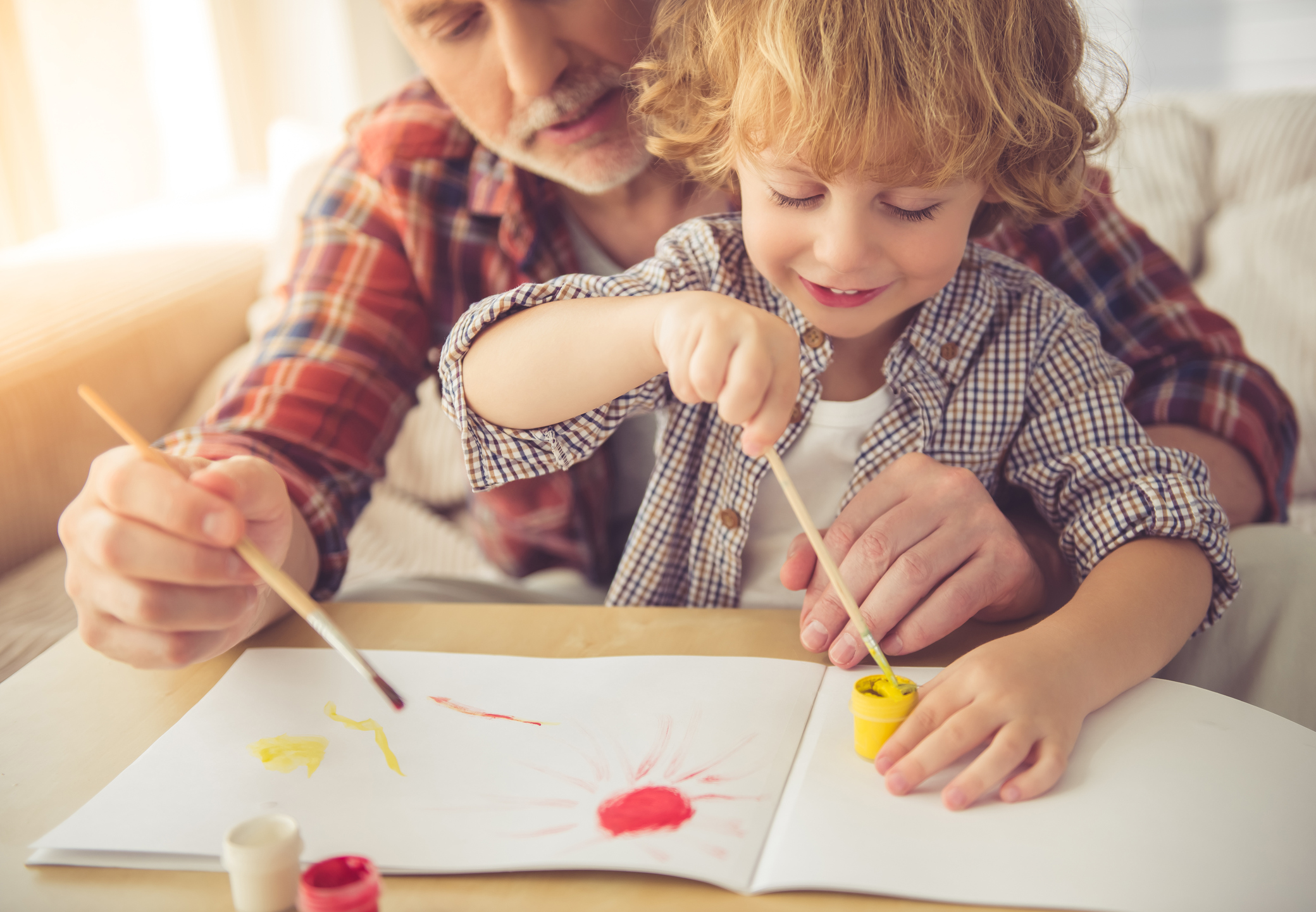 A grandad helps his grandson do some painting (Thinkstock/PA)