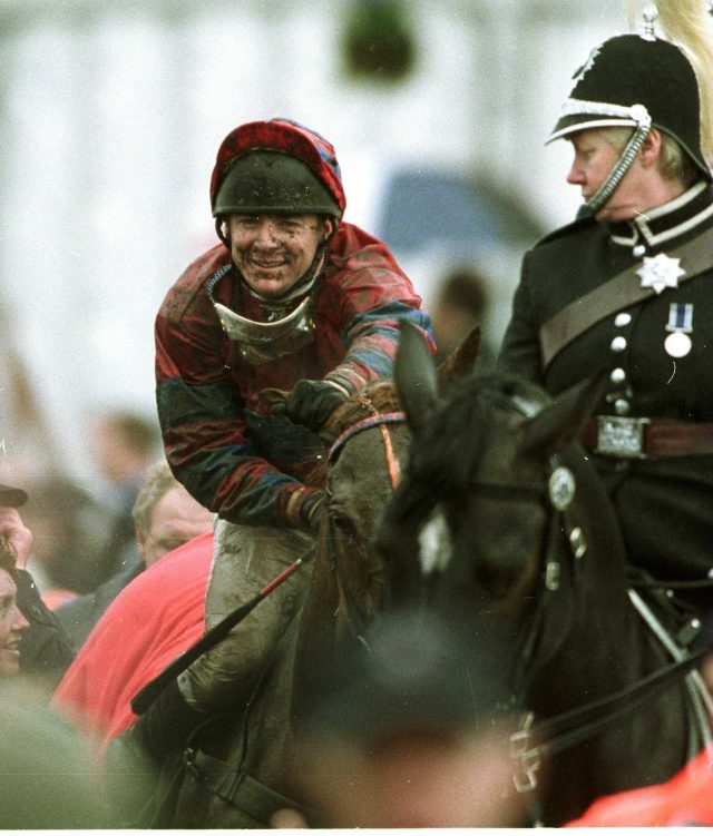 A mud-splattered Richard Guest wins the Grand National in 2001. He has a nice horse on his hands in Lough Salt