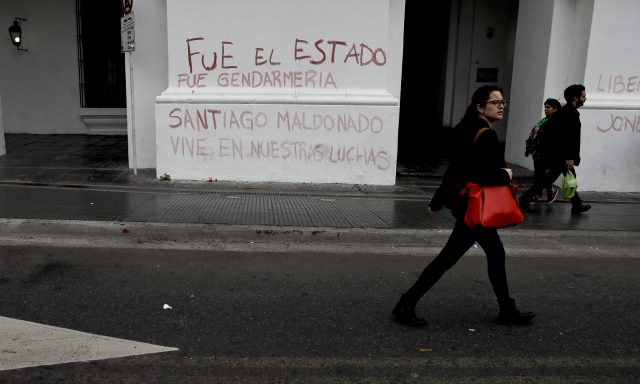 A woman passes graffiti that reads in Spanish: