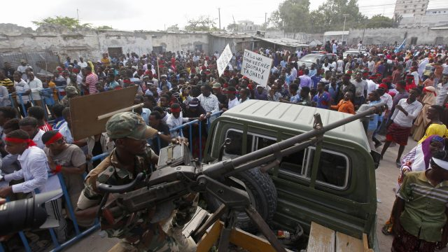 A Somali soldier sits with a machine gun on top a truck as protesters march