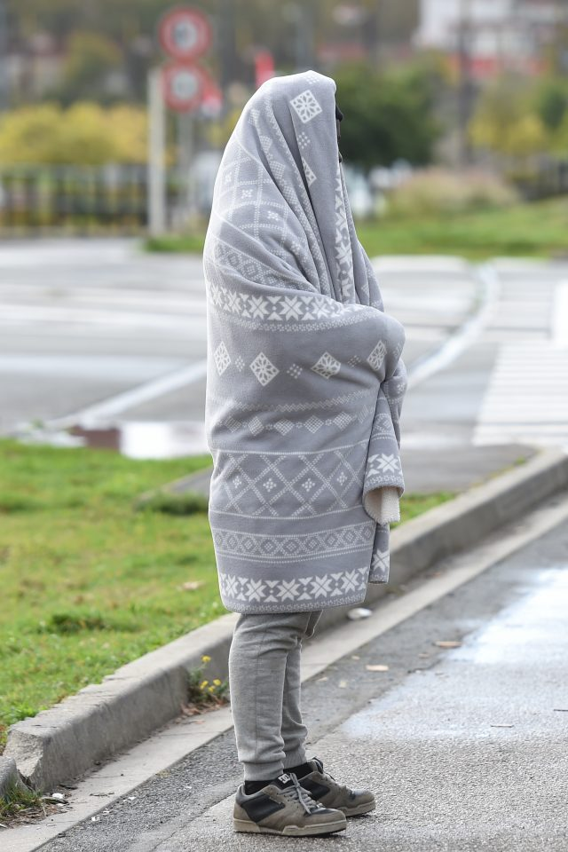 A migrant from Ethiopia uses a donated blanket to keep warm on the streets of Calais
