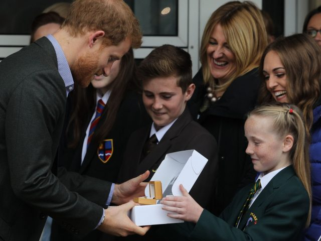 Prince Harry is presented with a Passchendaele 100 Poppy Pin by 11-year-old Phoebe Taylor