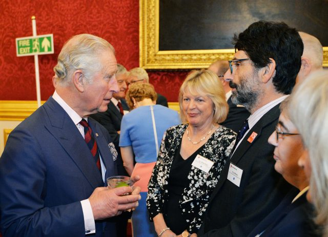 The Prince of Wales talks to guests at a reception for British Red Cross volunteers at St James's Palace