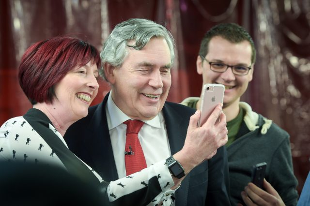Former Labour prime minister Gordon Brown poses for selfies after giving a speech on business and the automotive industry at Coventry University